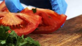 Il cuoco sta tagliando la fetta del pomodoro a metà sulla tavola in cucina domestica stock footage