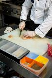 Il cuoco taglia la carne sul bordo bianco accanto alla scatola con le spezie in assortimento fotografia stock