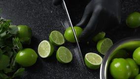 Il cuoco taglia le calce mature dal grande coltello tagliente sul tavolo da cucina scuro della roccia, facente del mojito, frutta archivi video