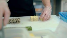 Il cuoco taglia un rotolo giapponese con sesamo bianco stock footage