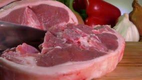 Il cuoco taglia una bistecca dell'agnello con un coltello stock footage