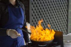 Il cuoco in un grembiule blu sta facendo una pausa la stufa con un burnin fotografia stock