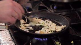 Il cuoco in una padella della ghisa dà i funghi e la cipolla a cucchiaiate stock footage