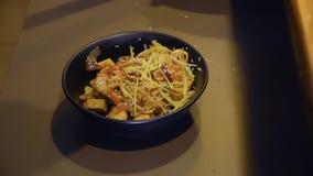 Il cuoco unico aggiunge il fagiolino ed il sesamo agli ingredienti fritti per la minestra di miso in una ciotola video d archivio