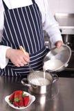 Il cuoco unico aggiunge il latte in una vaschetta Fotografia Stock Libera da Diritti