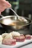Il cuoco unico aggiunge il sause alle bistecche di manzo, backgroung scuro Immagine Stock