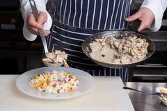 Il cuoco unico aggiunge la carne a risotto Fotografie Stock