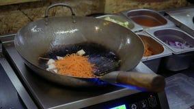 Il cuoco unico aggiunge la cipolla, la carota, il cavolo cinese ed il peperone dolce al tofu caldo sulla pentola archivi video