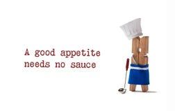 Il cuoco unico che cucina con il cucchiaio della cucina, la siviera di minestra ed appetito di proverbi A il buon non ha bisogno  Fotografia Stock