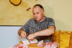 Il cuoco unico che taglia il bordo di legno della carne di maiale cruda ha preparato per cucinare immagini stock libere da diritti