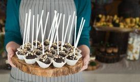 Il cuoco unico che tiene il vassoio di legno con il biscotto del cioccolato schiocca sui bastoni Fotografie Stock