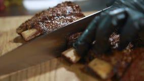 Il cuoco unico con esperienza sta tagliando le costole di carne di maiale in cucina del ristorante video d archivio