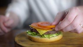 Il cuoco unico cucina l'hamburger e mette il pomodoro affettato fresco in, producendo gli hamburger al fast food, 4k UHD 60p Pror video d archivio