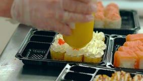 Il cuoco unico decora con il salmone rosso del caviale ha fritto i rotoli giapponesi con un'omelette stock footage