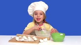 Il cuoco unico della bambina prepara l'alimento in uno studio sul blu, cottura di concetto video d archivio