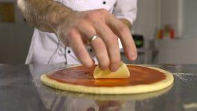 Il cuoco unico della mano mette il formaggio nella base della pizza sul primo piano della salsa al pomodoro archivi video