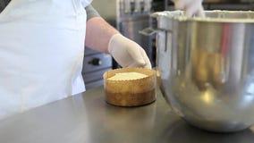 Il cuoco unico di pasticceria passa la pasta della glassa per il pane dolce di pasqua