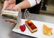 Il cuoco unico di pasticceria professionista sta decorando un dessert Fotografia Stock Libera da Diritti