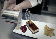 Il cuoco unico di pasticceria professionista sta decorando un dessert Fotografie Stock Libere da Diritti