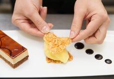Il cuoco unico di pasticceria sta decorando un dessert Fotografia Stock Libera da Diritti