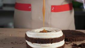 Il cuoco unico di pasticceria sta versando il caramello sul pan di Spagna del cioccolato Fabbricazione del dolce in forno video d archivio