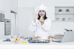 Il cuoco unico femminile tiene il bigné in cucina Fotografie Stock