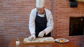 Il cuoco unico ha tagliato i cerchi dalla cucitura rotolata pasta cruda del biscotto su un bordo di legno video d archivio
