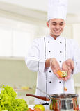 Il cuoco unico maschio ha messo un certo ingrediente nella pentola fotografie stock