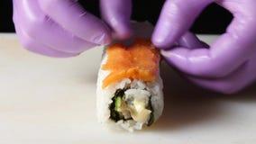 Il cuoco unico mette le fette del rotolo del riso di pesce Fine in su video d archivio