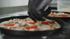 Il cuoco unico mette sopra i pomodori della pasta della pizza La pizza alla pizzeria video d archivio
