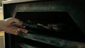 Il cuoco unico mette un pezzo di pesce di color salmone, di verdure al forno e di costole nel forno in un ristorante concetto di  video d archivio