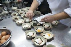 Il cuoco unico ottiene le uova à la coque sul piatto bianco messo sulla ciotola ceramica Immagini Stock