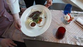 Il cuoco unico prende il piatto all'ospite nel ristorante stock footage