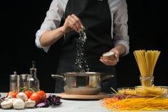 Il cuoco unico prepara gli spaghetti e la pasta, acqua salata, contro un fondo scuro, il concetto di cottura fotografie stock