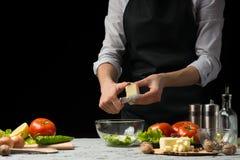 Il cuoco unico prepara un'insalata, affettante il feta, mozzarella, su un fondo scuro con uno spazio vuoto per scrivere immagine stock libera da diritti