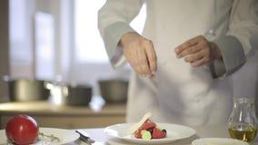 Il cuoco unico prepara un'insalata greca nella cucina archivi video