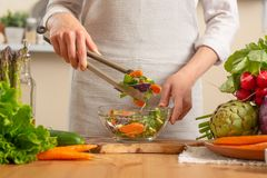 Il cuoco unico prepara un primo piano fresco e luminoso dell'insalata, su un fondo leggero Il concetto di alimento sano e sano di immagini stock