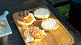Il cuoco unico produce gli hamburger in natura stock footage