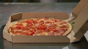 Il cuoco unico professionista mette ora la pizza cucinata dal forno dentro un contenitore di pizza Aspetti per la consegna video d archivio