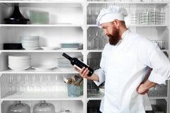Il cuoco unico sceglie una bottiglia di vino per gli ospiti Immagine Stock