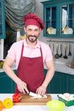 Il cuoco unico sorridente ha tagliato i funghi dal coltello sulla cucina in grembiule rosso fotografia stock