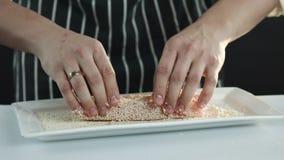 Il cuoco unico spruzza i semi di sesamo sul raccordo del tonno stock footage