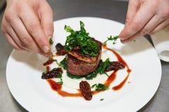 Il cuoco unico sta decorando la bistecca Fotografia Stock