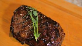 Il cuoco unico sta finendo la bistecca di manzo saporita del pasto con insalata per l'ospite del ristorante Tocco finale con la f stock footage