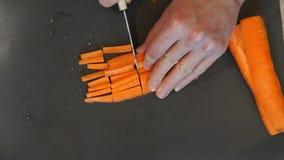 Il cuoco unico taglia la carota Processo di cottura Mani che tagliano carota Il cuoco unico affetta la carota video d archivio