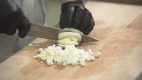 Il cuoco unico taglia le uova sul tagliere con il coltello in cucina al ristorante video d archivio