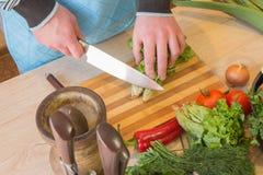 Il cuoco unico taglia le verdure in pasto Preparazione dei piatti, alimento sano Un uomo utilizza un coltello e cucina Cottura ma Immagine Stock Libera da Diritti