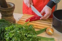 Il cuoco unico taglia le verdure in pasto Preparazione dei piatti, alimento sano Un uomo utilizza un coltello e cucina Cottura ma Fotografia Stock