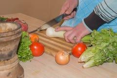 Il cuoco unico taglia le verdure in pasto Preparazione dei piatti, alimento sano Un uomo utilizza un coltello e cucina Cottura ma Fotografie Stock