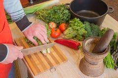 Il cuoco unico taglia le verdure in pasto Preparazione dei piatti Un maschio utilizza un coltello e cucina Fotografia Stock